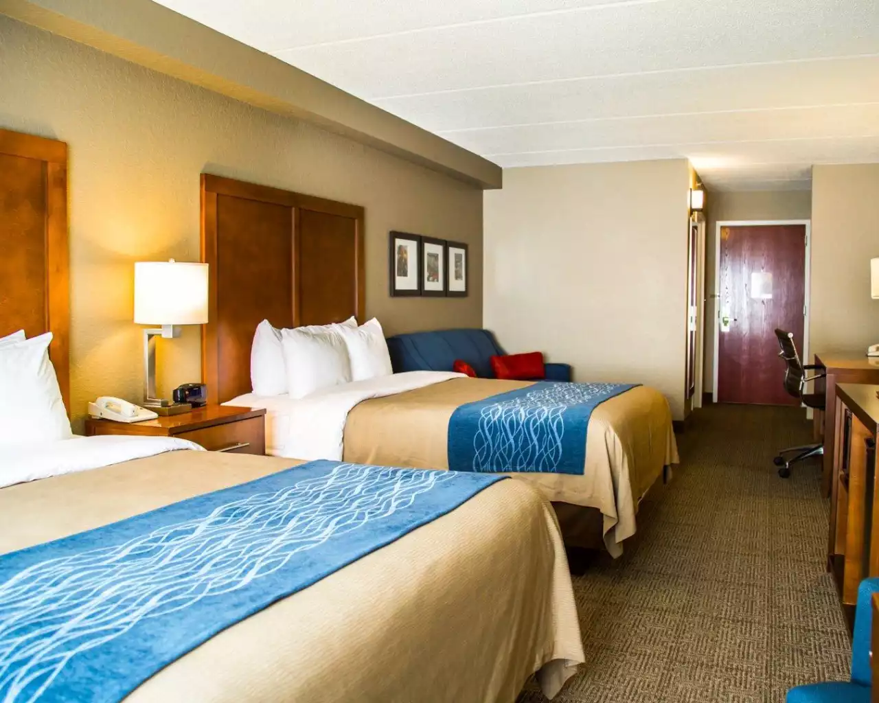 2 queen beds, a nightstand, lamp, and sleeper sofa in a Comfort Inn & Suites Sanford hotel room'