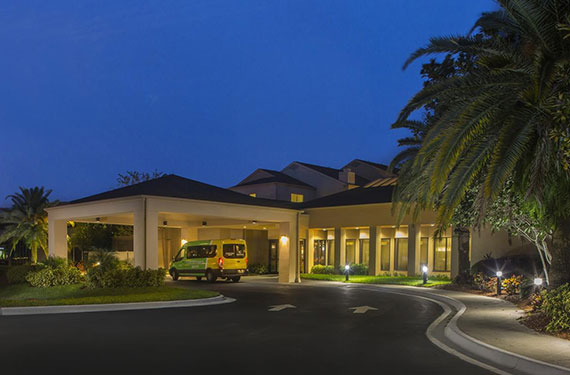 exterior view of Courtyard Marriott Orlando Airport hotel lobby entrance at night'