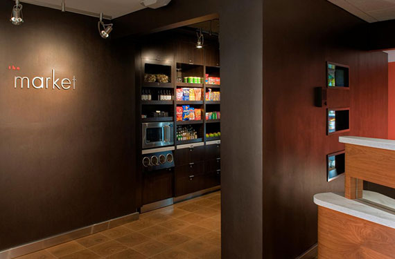 Snacks and other refreshments next to front desk available for purchase at Courtyard Marriott Orlando Airport hotel lobby'