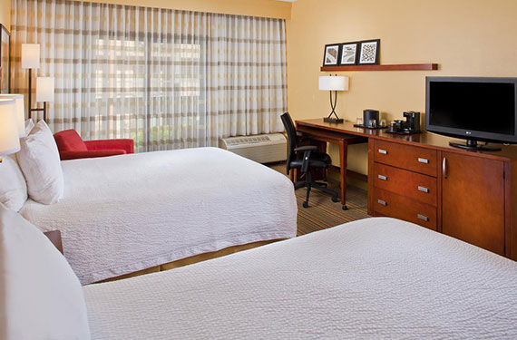 2 queen beds, desk, TV, and chair in a Courtyard Marriott Orlando Airport hotel room'
