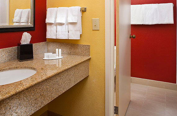 counter, mirror, and toilet in a Courtyard Marriott Orlando Airport hotel room bathroom'