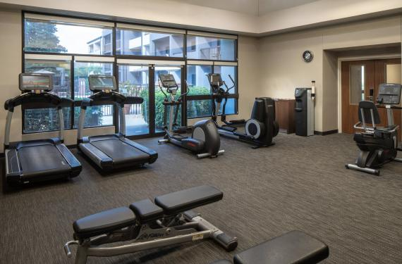 fitness center at Courtyard Marriott Orlando Airport with treadmills, exercise bikes, weights and bench