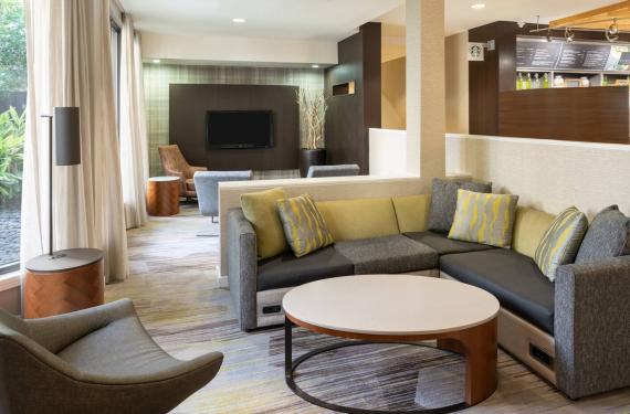 common area in lobby of Courtyard Marriott Orlando Airport hotel with seating, and tables'