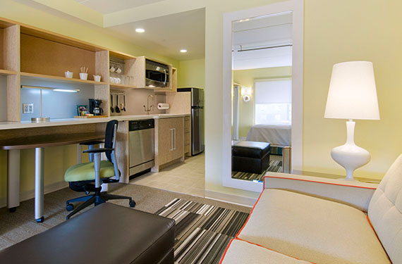 desk, sleeper sofa, and mirror in a Home2 Suites Orlando Airport hotel room'