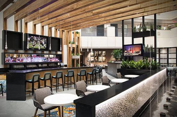 bar, bar stools, and dining area with tables and chairs at Embassy Suites Orlando Airport hotel'