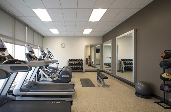 gym equipment and machinery, including weights and treadmills in Embassy Suites Orlando Airport hotel fitness center
