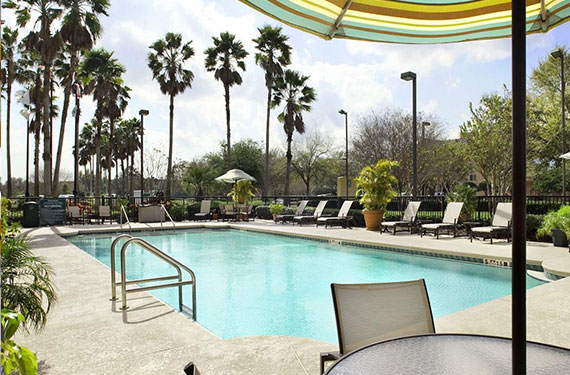 outdoor pool, lounge chairs, and umbrellas at Embassy Suites Orlando Airport hotel 