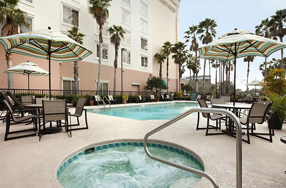 view of hot tub, outdoor pool, umbrella tables and chairs at Embassy Suites Orlando Airport hotel '