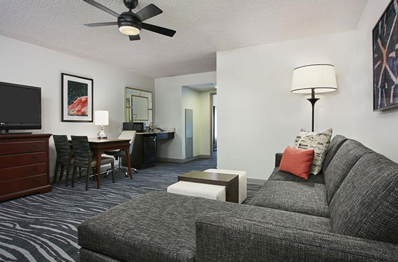 sleeper sofa, coffee table, dresser, TV, tables and chairs in a Embassy Suites Orlando Airport hotel room'