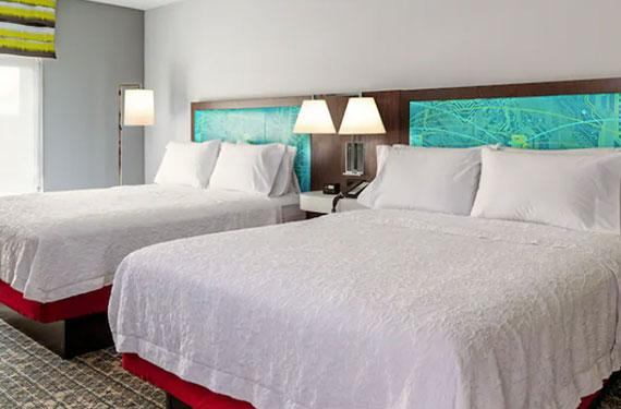 2 queen beds, night stand, and lamps in Hampton Inn Cape Canaveral hotel room