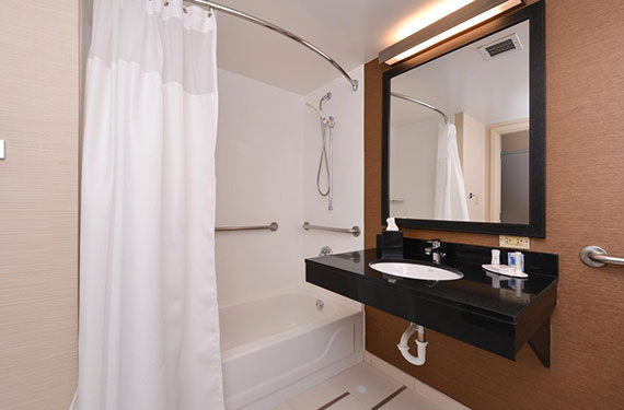 tub, shower, counter, sink, and mirror in a Fairfield Inn Orlando Airport hotel room'