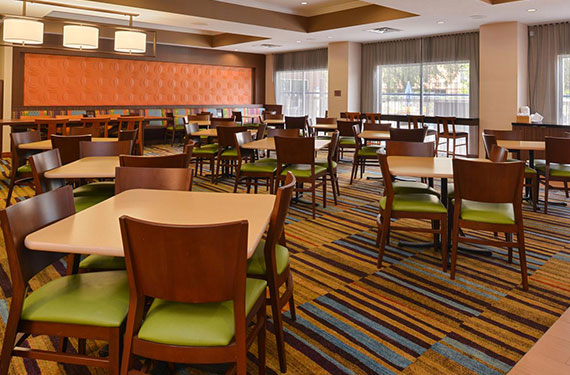 dining tables and chairs at complimentary buffet breakfast buffet at Fairfield Inn Orlando Airport hotel 