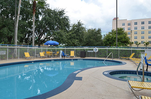 outdoor pool, pool, hot tub, and lounge chairs at Fairfield Inn Orlando Airport hotel